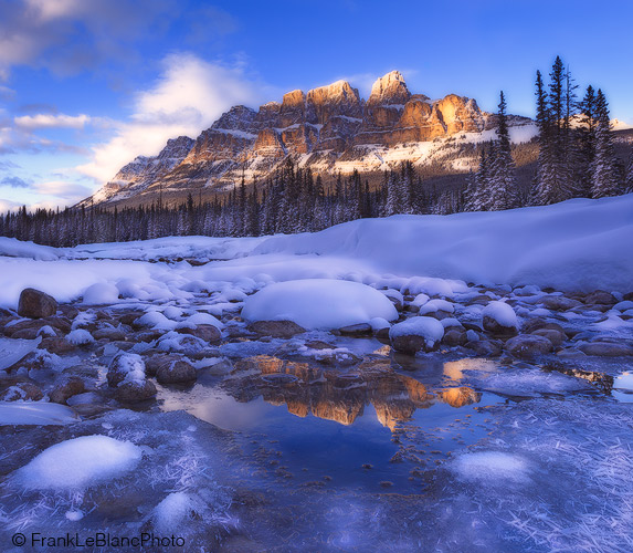 Castle mountain is reflected in a small pool of water surrounded by hoarfrost and ice. The Bow river is hidden by the mid-ground...