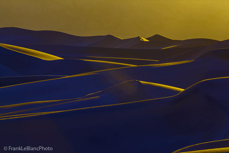Mesquite Flat Dunes at sunset presents a scene of layer upon layer of intersecting lines and lighted shapes. Yellow light is...