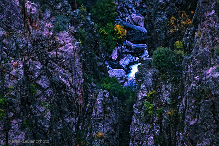 Looking down through the steep walls and escarpments of the Black Canyon of the Gunnison River, the actual river briefly appears...
